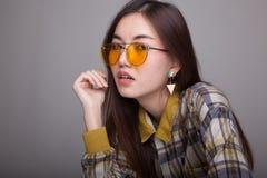 Mulher asiática nova bonita com óculos de sol amarelos Fotografia de Stock Royalty Free