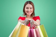 Mulher asiática nova bonita com os sacos de compras coloridos sobre o azul Fotografia de Stock Royalty Free