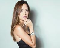 Mulher asiática nova bonita com relógio de pulso vestindo Imagens de Stock Royalty Free