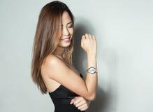 Mulher asiática nova bonita com relógio de pulso vestindo Foto de Stock