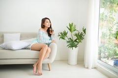 Mulher asiática nova bonita que bebe seu chá da manhã sobre um brea Fotografia de Stock Royalty Free