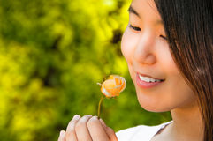 Mulher asiática nova bonita que olha o botão de Rosa fotografia de stock royalty free