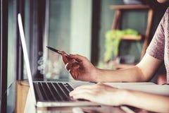 Mulher asiática nova bonita que trabalha em uma cafetaria com portátil do computador fotos de stock