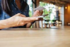 Mulher asiática nova bonita que usa o smartphone e guardando o cartão para o pagamento em linha de compra Conceito da compra com  Imagens de Stock Royalty Free