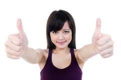 A mulher asiática nova bonito que dá os polegares levanta o sinal Fotografia de Stock Royalty Free