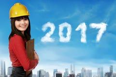 Mulher asiática nova com capacete de segurança e um número de 2017 anos Fotografia de Stock Royalty Free