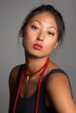 Mulher asiática nova com grânulos vermelhos Imagem de Stock Royalty Free