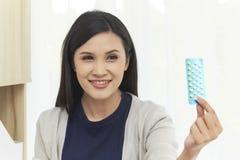 A mulher asiática nova com impede comprimidos fotos de stock royalty free