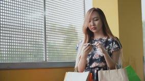 Mulher asiática nova com sacos de compras usando o smartphone vídeos de arquivo