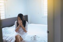 Mulher asiática nova com sopro do frio e nariz ralo na cama, mulher doente que espirra, conceito da saúde foto de stock royalty free
