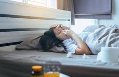 Mulher asiática nova com sopro do frio e nariz ralo na cama, espirrar doente da mulher imagem de stock royalty free