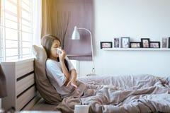 Mulher asiática nova com sopro do frio e nariz ralo na cama, espirrar fêmea doente, conceito da saúde imagem de stock