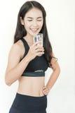 Mulher asiática nova da felicidade no sportswear preto que guarda o vidro de imagem de stock royalty free