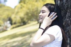 A mulher asiática nova deve apreciar o estilo de vida e a música de escuta fotos de stock royalty free