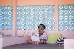 Mulher asiática nova do moderno atrativo e feliz que trabalha com o laptop em relaxar fora o local de trabalho que aprecia o suce fotos de stock