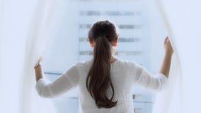 Mulher asiática nova do retrato bonito para abrir a janela que olha e que diz o olá! no quarto filme