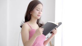 A mulher asiática nova do retrato bonito relaxam e a posição do lazer que aprendem com o livro de leitura para o exame em casa video estoque