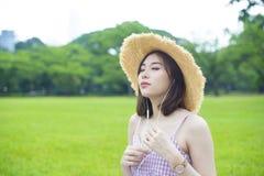 A mulher asiática nova está escutando o telefone principal do throuh da música imagens de stock