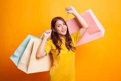 Mulher asiática nova feliz com o saco de compras no vestido amarelo Fotografia de Stock Royalty Free