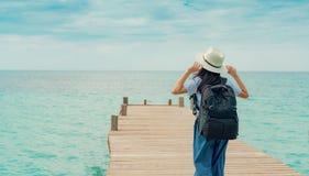 Mulher asiática nova feliz na forma do estilo ocasional com chapéu de palha e trouxa Relaxe e aprecie o feriado na praia tropical imagem de stock royalty free