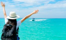 Mulher asiática nova feliz na forma do estilo ocasional com chapéu de palha e trouxa Relaxe e aprecie o feriado na praia tropical fotografia de stock royalty free