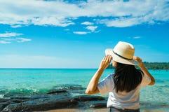 Mulher asiática nova feliz na forma do estilo ocasional com suporte do chapéu de palha na praia do mar do recurso em férias de ve fotos de stock