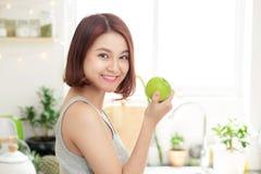 Mulher asiática nova feliz que come Apple verde na cozinha Dieta dado Fotos de Stock Royalty Free