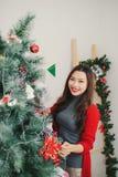 Mulher asiática nova feliz que está o ce próximo da árvore de Natal em casa fotos de stock