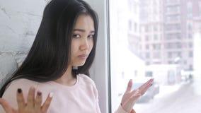 Mulher asiática nova na frustração e na raiva, sentando-se na janela video estoque