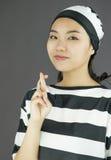 A mulher asiática nova no uniforme dos prisioneiros que mostra a cruzou os dedos Imagem de Stock