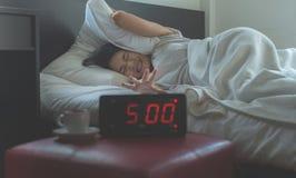 A mulher asiática nova odeia obter forçada acordando cedo o pulso de disparo do ` de 5 o, despertador foto de stock royalty free