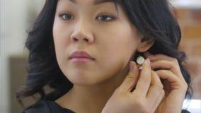 A mulher asiática nova põe sobre brincos bonitos filme