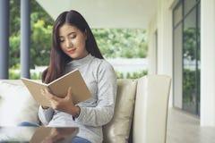 Mulher asiática nova para apreciar a ler a nota em um caderno, sentando-se no sofá em casa conceitos de sentimento do abrandament fotografia de stock royalty free