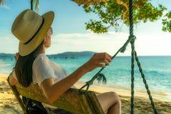 Mulher asiática nova para sentar-se e relaxar em balanços no beira-mar em férias de verão Vibrações do verão Curso da mulher apen fotografia de stock royalty free