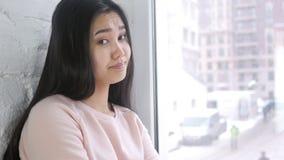 Mulher asiática nova que agita a cabeça para rejeitar e negar, sentando-se na janela video estoque