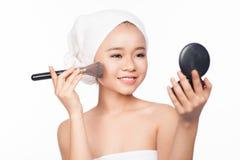 Mulher asiática nova que aplica o pó com uma escova cosmética em sua cara Vista à composição do espelho Isolado no fundo branco Imagens de Stock