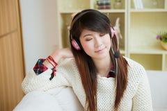 Mulher asiática nova que aprecia a música Imagem de Stock