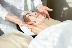 Mulher asiática nova que aprecia a massagem de cara imagens de stock