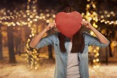Mulher asiática nova que cobre sua cara com a forma vermelha do coração Imagens de Stock Royalty Free