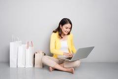 Mulher asiática nova que compra em linha em casa sentando-se além da fileira de Fotografia de Stock Royalty Free