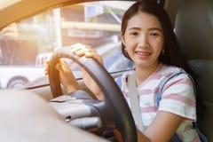 A mulher asiática nova que conduz o carro mantém a roda girar em torno do sorriso fotos de stock royalty free