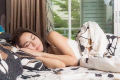 Mulher asiática nova que dorme em sua cama, está descansando com olhos c foto de stock