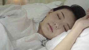 Mulher asiática nova que dorme na cama filme