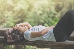 Mulher asiática nova que dorme no banco de madeira no parque Foto de Stock