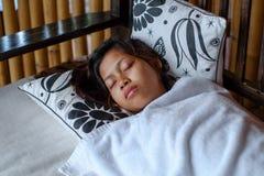 Mulher asiática nova que dorme pacificamente no balcão durante férias de verão foto de stock