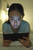 Mulher asiática nova que encontra-se na cama e que usa a tabuleta digital Fotos de Stock Royalty Free