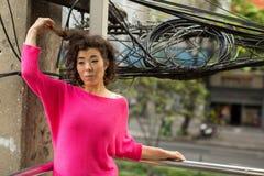 Mulher asiática nova que está em uma passagem superior na cidade metropolis foto de stock royalty free