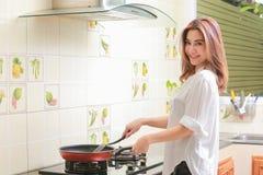Mulher asiática nova que faz a omeleta em uma cozinha Fotos de Stock Royalty Free