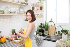 Mulher asiática nova que faz a salada na cozinha que sorri e que ri h foto de stock royalty free