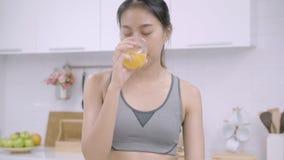 Mulher asiática nova que faz a salada o alimento saudável ao usar a tabuleta para olhar a receita e beber o suco de laranja na co vídeos de arquivo